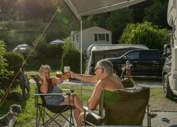 Campinggäste stoßen vor ihrem Wohnmobil Stellplatz mit Getränken an